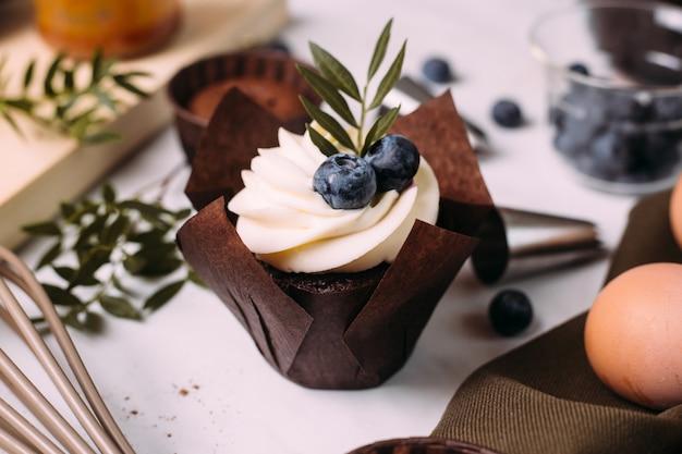 クリームとブルーベリーのキッチンテーブルの上のカップケーキ