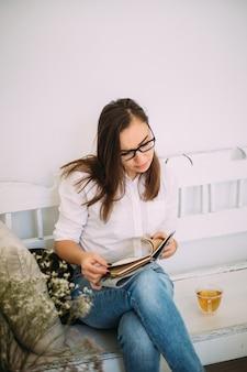 Красивая молодая женственная женщина в стильных очках, одетая в модную повседневную одежду, сидит на скамейке с ноутбуком и чашкой чая