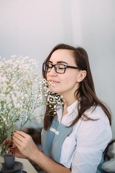 Малый бизнес. флорист девушка сосредоточена в цветочном магазине. яркая студия цветочного дизайна, декора. доставка цветов, создание заказов