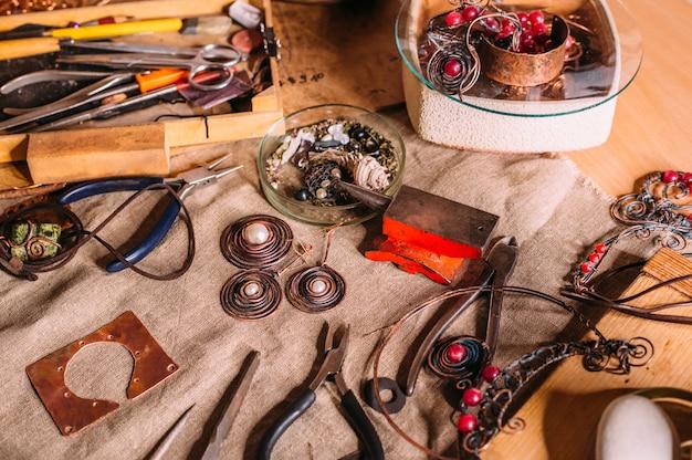 Инструменты ручной работы из медной проволоки на столе с аксессуарами. ремесленная концепция искусства
