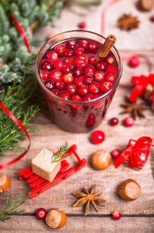Стакан клюквенного напитка, клюква, палочки корицы, аниса звезды на фоне деревянные. рождественские зимние напитки.