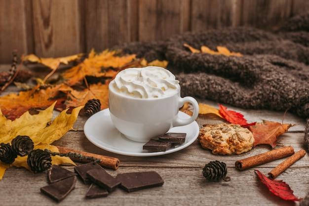 秋、紅葉、コーヒーの蒸しカップ、木製のテーブルに暖かいスカーフ。