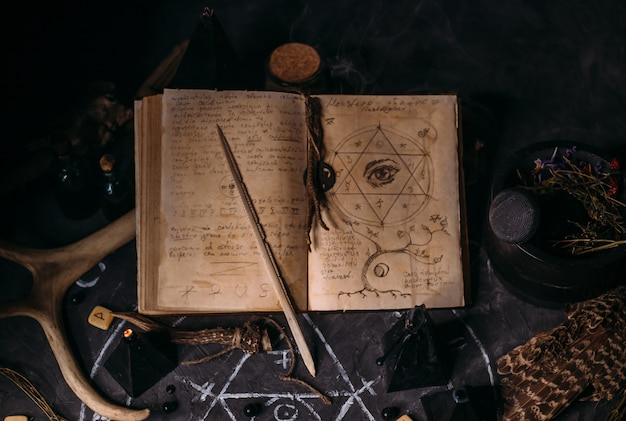 魔法の呪文、ルーン文字、魔女のテーブルに黒いキャンドルで古い本を開きます。オカルト、難解な占い、ウィッカのコンセプトです。ハロウィンシーン