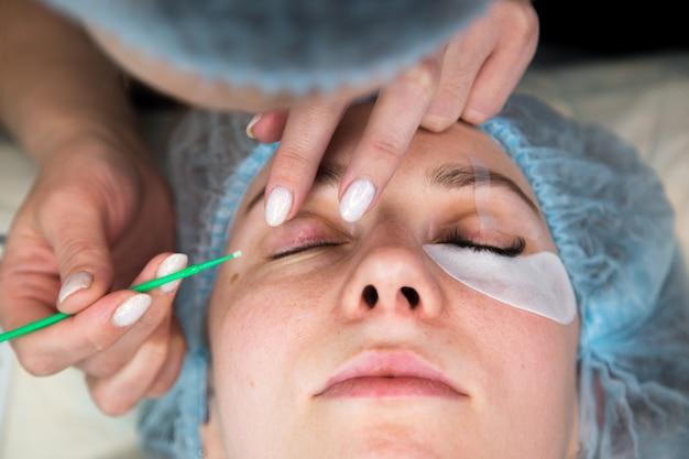 Процедура наращивания ресниц. женский глаз с длинными ресницами. ресницы, конец вверх, макрос, селективный фокус.