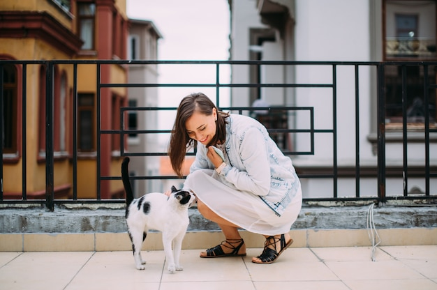 Милая девушка гладит бездомную кошку на улице и улыбается