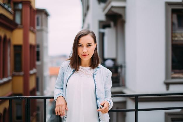 Красивая молодая женщина на балконе смотрит в камеру