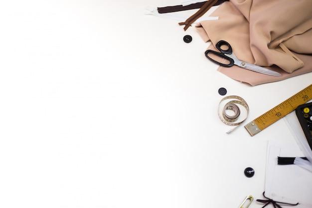 Швейные аксессуары и ткани на белом фоне. швейные нитки, иголки, булавки, ткань, пуговицы и сантиметр для шитья. вид сверху, плоская
