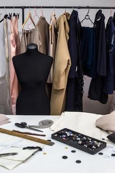 Модная креативная дизайнерская концепция интерьера с манекеном-манекеном и стильной модной модной одеждой на вешалках, на швейном рабочем месте, в ателье, швейной мастерской