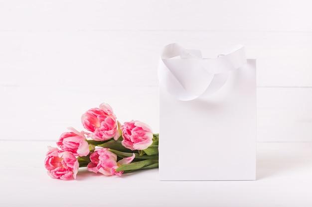 Белая бумажная сумка на деревянной предпосылке. букет из красивых розовых тюльпанов. праздничный макет.