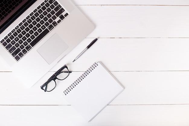Компьютер, пустой блокнот, ручка и очки. домашний офис и концепция карьеры.