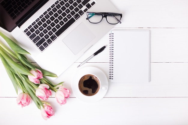Розовые тюльпаны с праздничным настроением и кофе на белых деревянных досках.