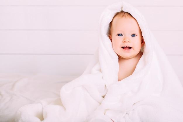 Милый ребенок с голубыми глазами, завернутый в белое полотенце, а капюшон смотрит в камеру.
