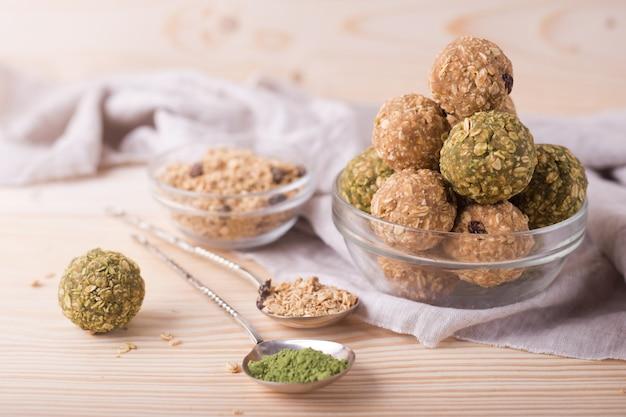 健康的な有機エネルギーのグラノーラは、ナッツ、レーズン、抹茶、ハチミツに噛まれます-ビーガンベジタリアン生スナックまたは食事