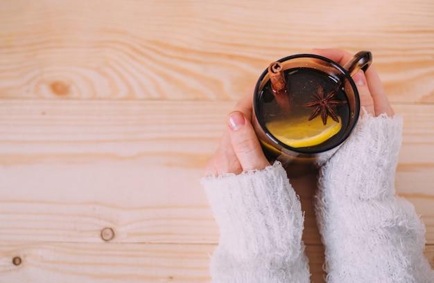 レモンと温水のカップを保持している女性の手のクローズアップ