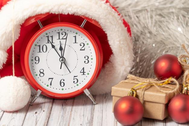 Красный старинный будильник в шапке санта-клауса и подарочная коробка на деревянном столе, украшенном гирляндой и красными елочными шарами на новый год или рождество. почта, курьер или служба доставки концепции. копировать пространство