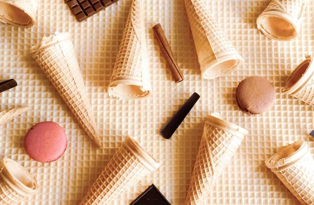 ワッフル生地のテーブルにアイスクリームコーンとマカロン