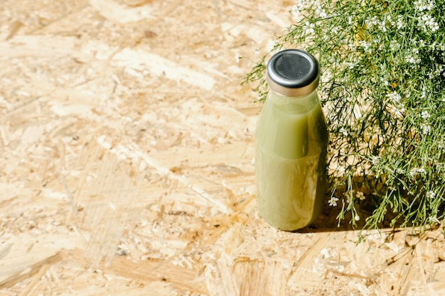 Зеленый детокс сок рядом с кустом