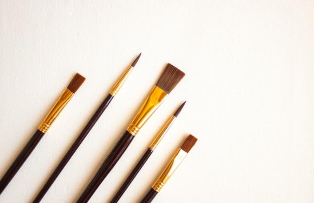 Набор кистей для рисования на белом фоне, плоская планировка.