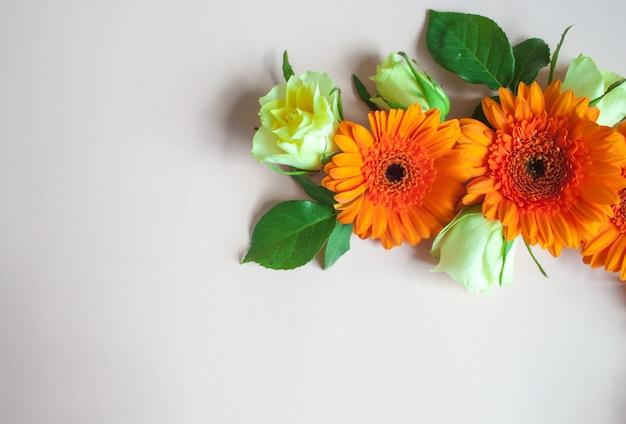 オレンジ色のガーベラの花と白い背景のバラで作られたフレーム。お祝いのロマンチックなコンセプト。