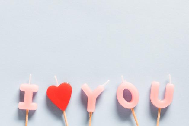 パステルブルーの背景にキャンドルを愛しています。バレンタインデーのコンセプトの背景。