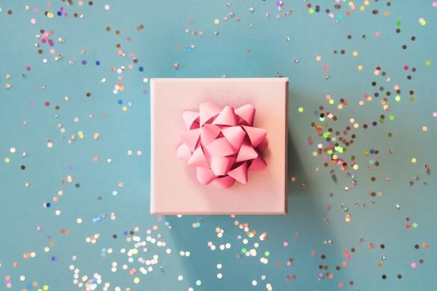 Белая серебряная подарочная коробка с розовым бантом на зеленом синем фоне в модной плоской композиции с золотыми блестками.