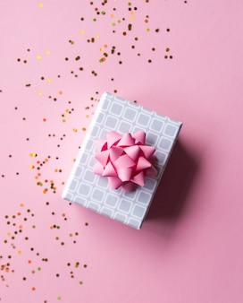 ピンクの弓と黄金の輝きと最小限の組成の背景を持つ銀のギフトボックス。