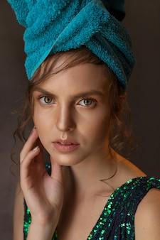 光沢のあるグリーンブルーのドレスと頭にタオルの女の子