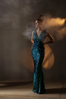 光沢のある緑と青のドレスの女の子が暖かい光、煙、暗闇の中に立っています。