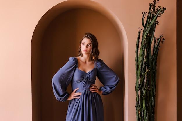 ベージュの部屋でポーズをとってカジュアルな青いドレスの若いブルネットの少女