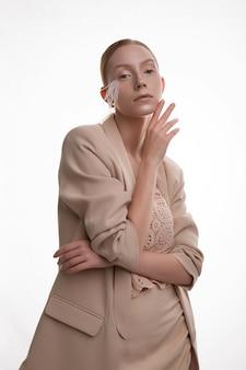 Молодая блондинка с художественным макияжем позирует в бежевом костюме юбки