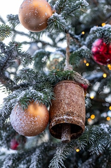 Елка украшена винтажными колокольчиками и шариками на размытом абстрактном игристом