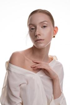 ホワイトスタジオでポーズをとって白い衣装でアートメイクと若いブロンドモデル