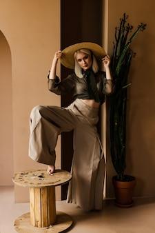 美しい若いブロンドモデルは麦わら帽子と緑の透明なブラウスでポーズをとってください。