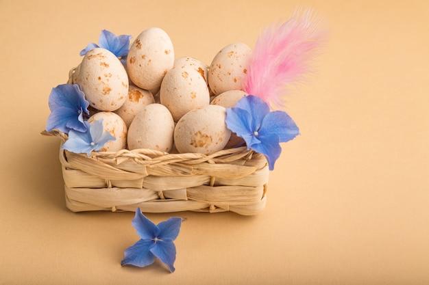 Пасхальный фон с бежевыми яйцами марципана и весенними цветами