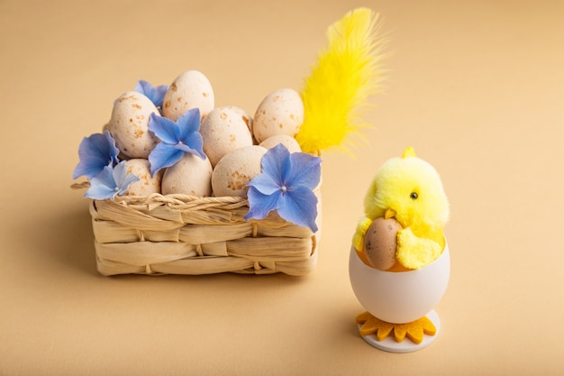 ベージュのマジパンイースターエッグ、ひよこ、春の花とイースターの背景
