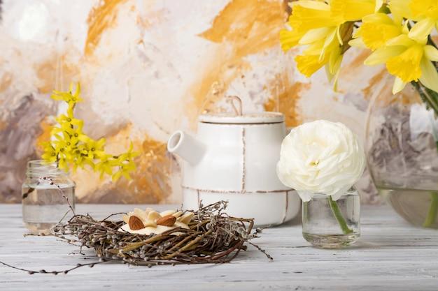 巣と白いビンテージ木製テーブルの上に花のケーキ