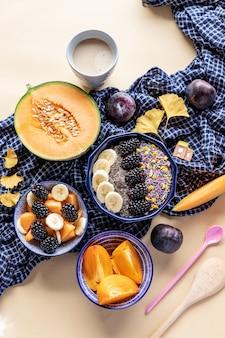 Чаша для завтрака с овсянкой, йогуртом, ежевикой, хурмой, дыней и чиа, вид сверху