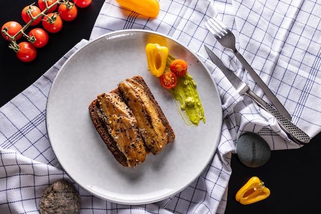 ライトグレーのプレート、上面にライ麦パンと自家製スモークニシンサンドイッチ