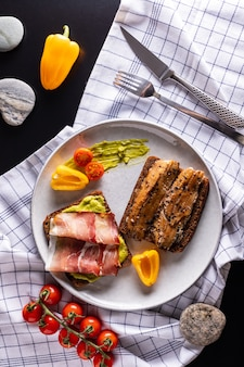 ライトグレーのプレート、上面にライ麦パンと自家製スモークニシンとシュヴァルツヴァルトのハムのサンドイッチ