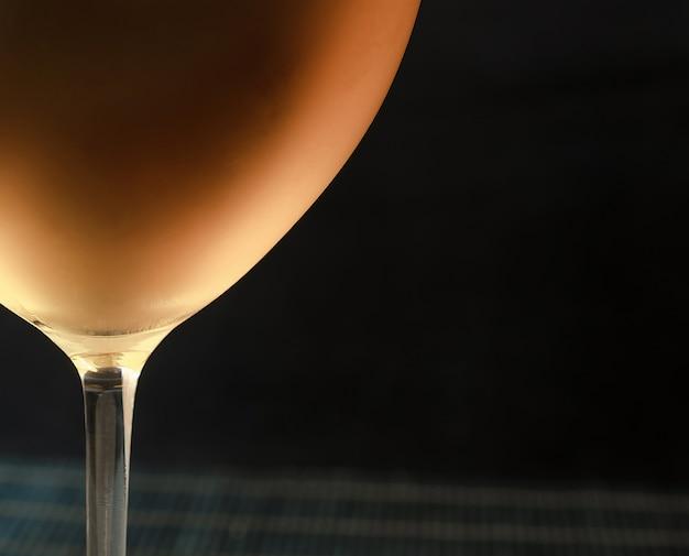 Белое вино в бокале, черный стол