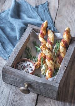 Обернутые беконом хлебные палочки на деревянном подносе