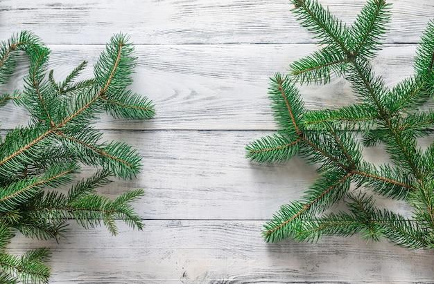 木製の背景にクリスマスツリーの枝