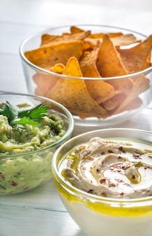 Чаши из хумуса и гуакамоле с чипсами из тортильи