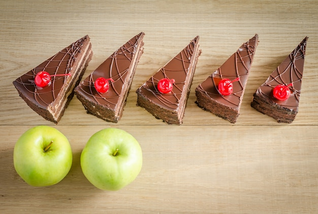 Кусочки шоколадного торта и два яблока