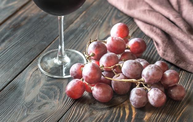 Стакан красного вина с гроздью красного винограда