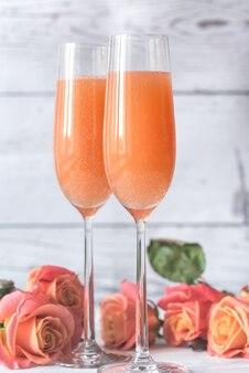 Два бокала коктейля беллини с букетом роз