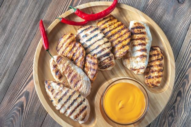 Жареная куриная грудка на деревянном подносе
