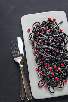 ザクロの種子と黒のパスタ