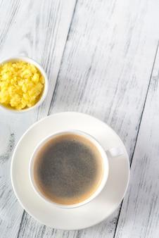 ギーのボウルとコーヒーのカップ