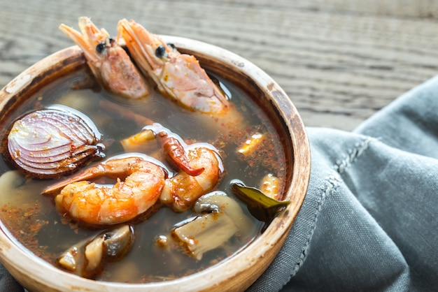 Чаша тайский том ям суп на деревянный стол